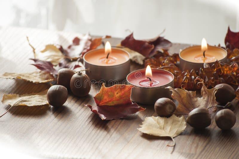 Três velas ardentes, folhas de outono coloridas e bolotas do carvalho vermelho do norte e da colar ambarina foto de stock