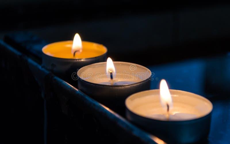 Três velas ardentes na linha imagens de stock royalty free
