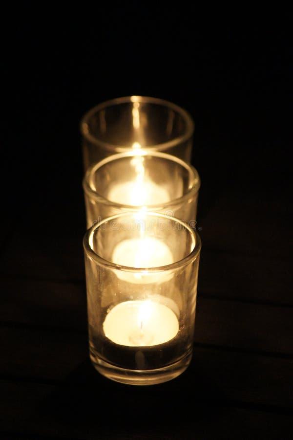 Três velas de cintilação iluminam acima a noite foto de stock royalty free