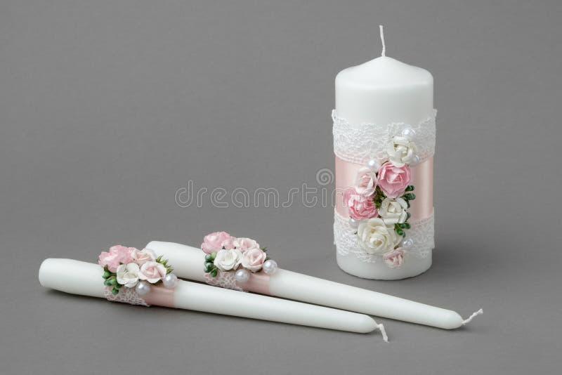 Três velas decoradas com rosas bonitas, pérolas, as fitas de seda cor-de-rosa e o laço foto de stock