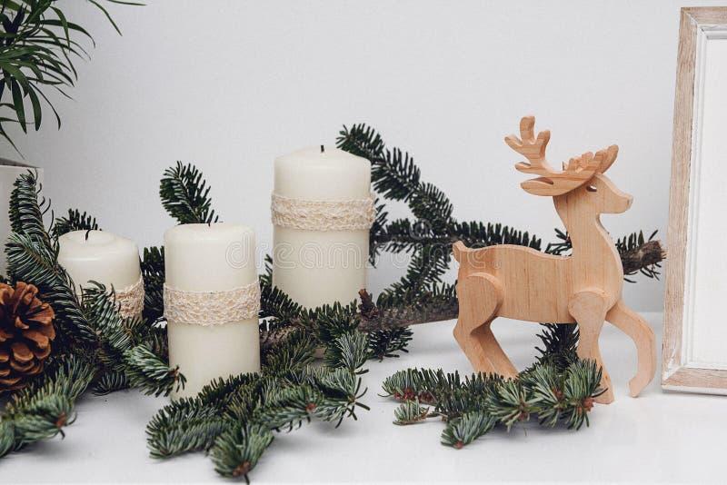 Três velas do Natal, pinecone, quinquilharias, ramo do pinho, gsarland e cervos de madeira na tabela branca Celebração e imagens de stock royalty free