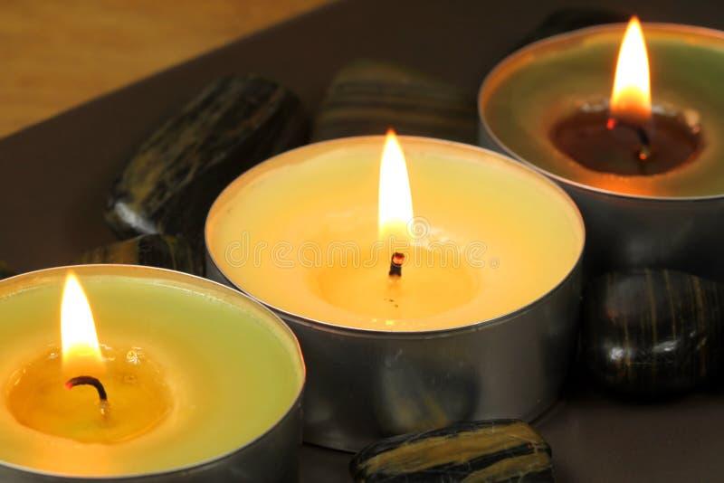 Três velas e pedras imagens de stock royalty free