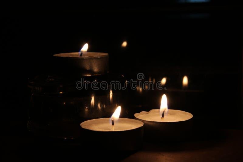Três velas na obscuridade fotografia de stock