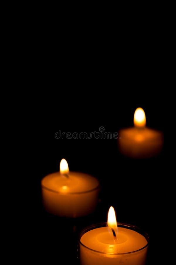 Três velas na obscuridade fotos de stock