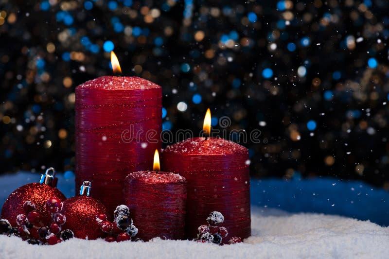 Três velas vermelhas na neve foto de stock royalty free