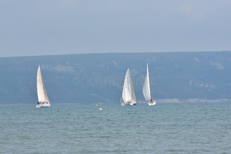 Três veleiros em águas litorais foto de stock