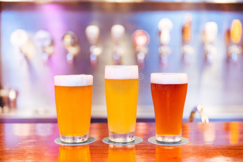 Três vidros da cerveja do ofício com espuma e de cores diferentes da luz à obscuridade no contador de madeira com borrão e bokeh imagem de stock