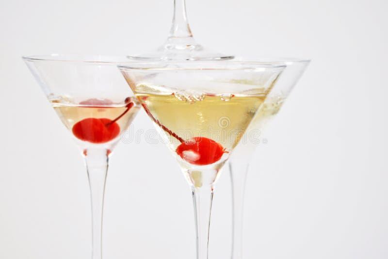 Três vidros de martini, enchidos com o champanhe com as cerejas e o nitrogênio líquido, criando o vapor, na forma da pirâmide fotos de stock royalty free