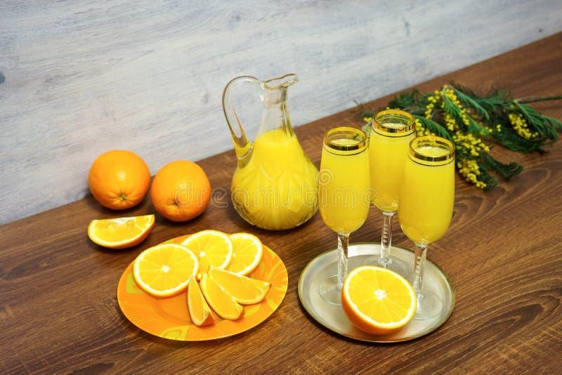 Três vidros do cocktail da mimosa, um filtro com suco de laranja, laranjas frescas, ramo da mimosa em uma tabela de madeira imagens de stock