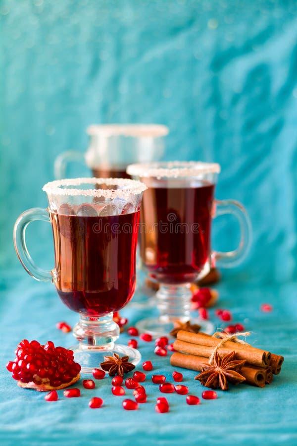 Três vidros do vinho ferventado com especiarias quente com sementes e especiarias da romã fotos de stock