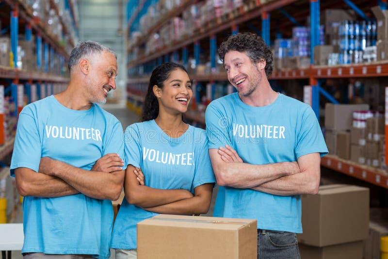 Três voluntários felizes que estão com os braços cruzados fotos de stock
