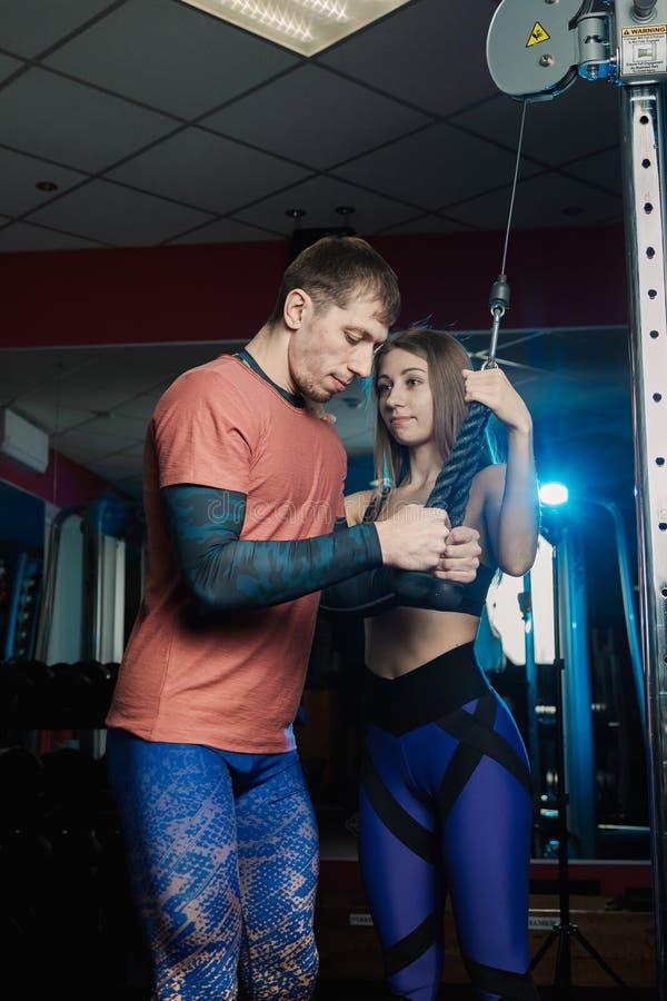 Tríceps atlético hermoso de los trenes del hombre en el bloque bajo la orientación de un instructor en el gimnasio imagen de archivo