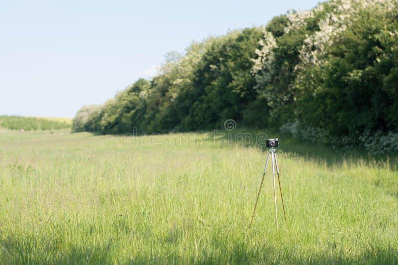 Trípode de cámara del vintage en prado verde imagen de archivo libre de regalías