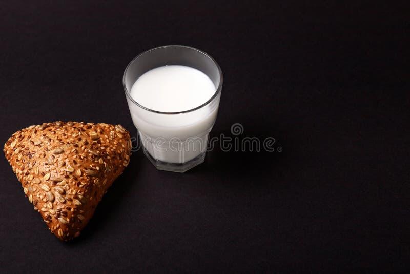 Trójgraniasta babeczka z ziarnami i mlekiem na czarnym tle Teksta miejsce obraz royalty free