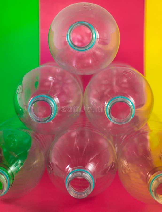 Trójgraniasta stos paczka 6 pusty i recyclable plastikowi bidony, bez nakrętek, błękitna foka na barwiony wibrującym, obraz stock
