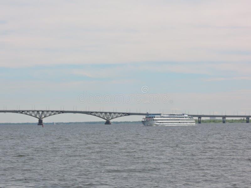 Trójpokładowy statek wycieczkowy pływa pod wielkim, pięknym mostem samochodowym na szerokiej, niebieskiej rzece w czysty letni dz obrazy royalty free