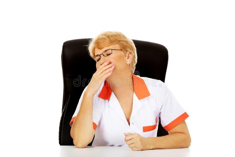 Trött äldre kvinnligt doktors- eller sjuksköterskasammanträde bak skrivbordet och gäspningarna royaltyfri foto