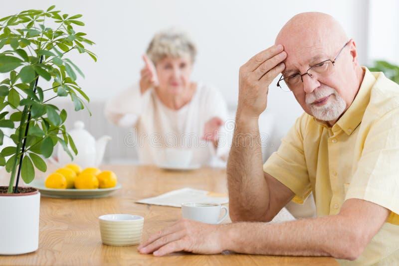 Trött äldre man som argumenterar med hans fru i morgonen royaltyfri foto