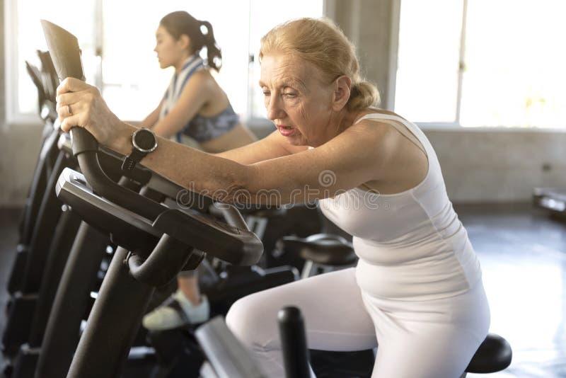 Trött öva roterande cykel för hög kvinna i konditionidrottshall royaltyfri bild