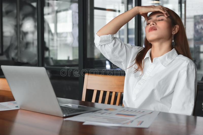 Trött överansträngt ungt asiatiskt lidande för affärskvinna från sträng fördjupning i arbetsplats royaltyfria foton