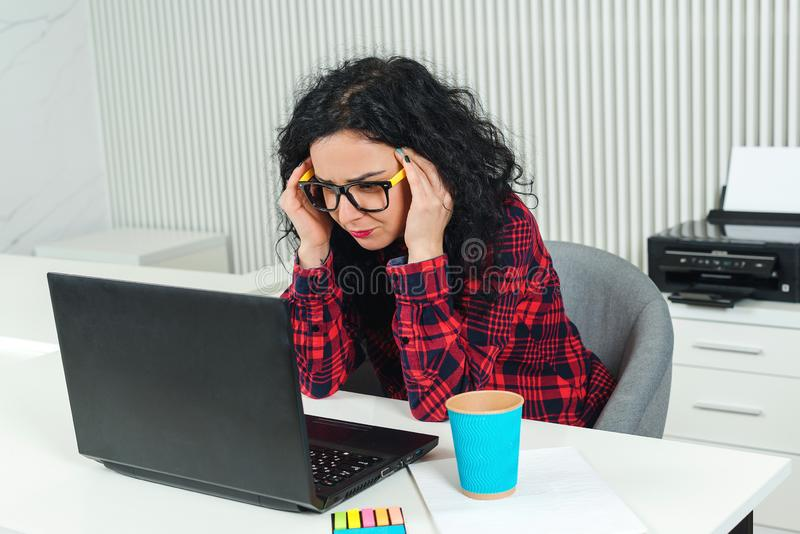 Trött affärskvinna på arbetsplatsen Stressad kvinna som arbetar på bärbara datorn i modernt kontor head holdingkvinna för hand hå royaltyfri fotografi