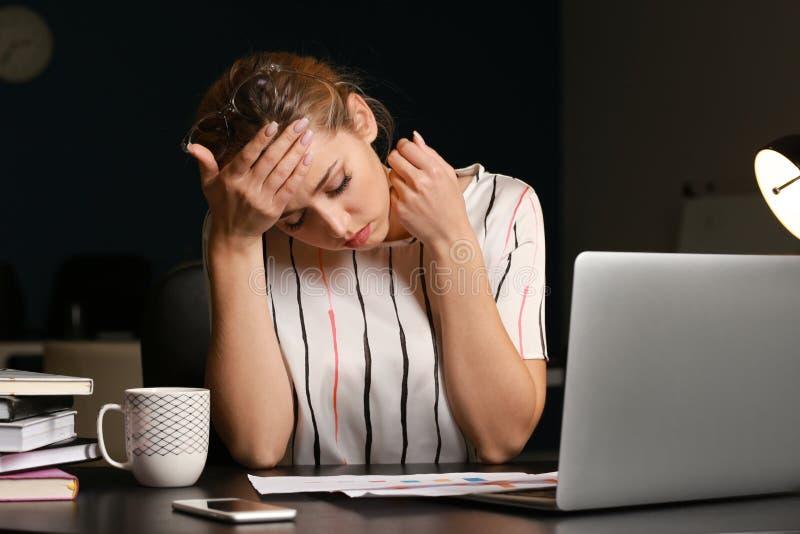 Trött affärskvinna som i regeringsställning arbetar sent i afton royaltyfri foto
