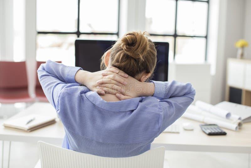Trött affärskvinna som rymmer hennes nacke arkivbilder