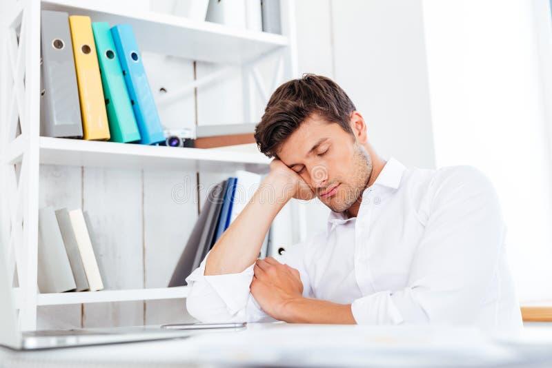 Trött affärsman för barn som sover på arbetsplatsen royaltyfria bilder