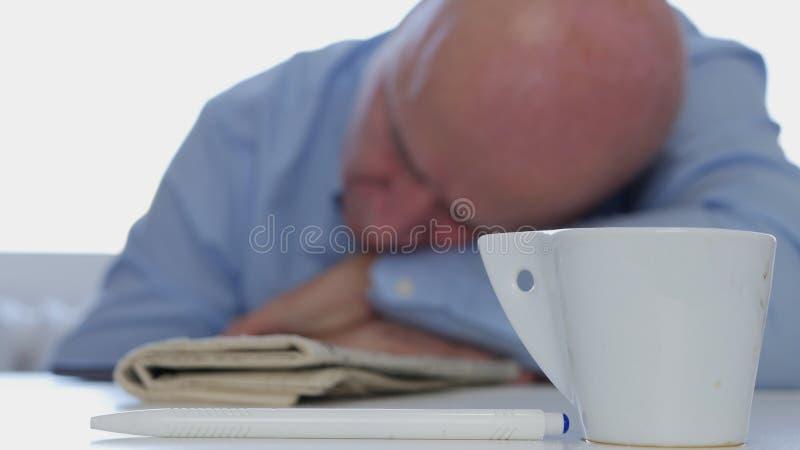 Trött affärsman Napping hemma med kaffe och tidningen på tabellen royaltyfri fotografi