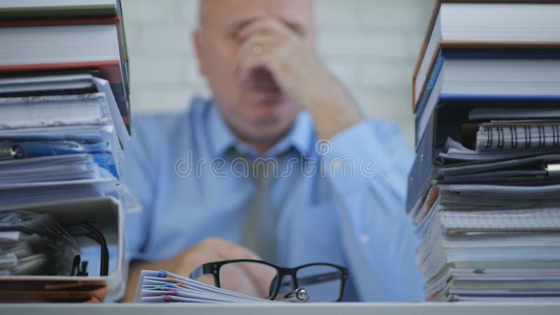 Trött affärsman Rubbing His Eyes med händer som sent arbetar i redovisande kontor royaltyfri fotografi