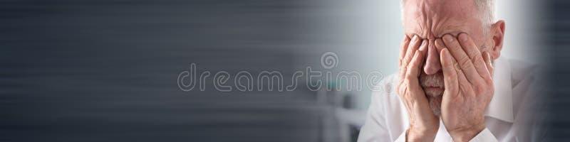 Trött affärsman som gnider hans ögon arkivfoto