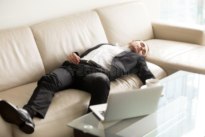 Trött affärsman som i regeringsställning sover på soffan arkivfoto