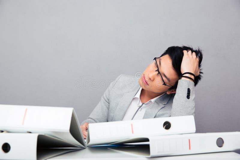 Trött affärsman som sover på tabellen royaltyfri bild