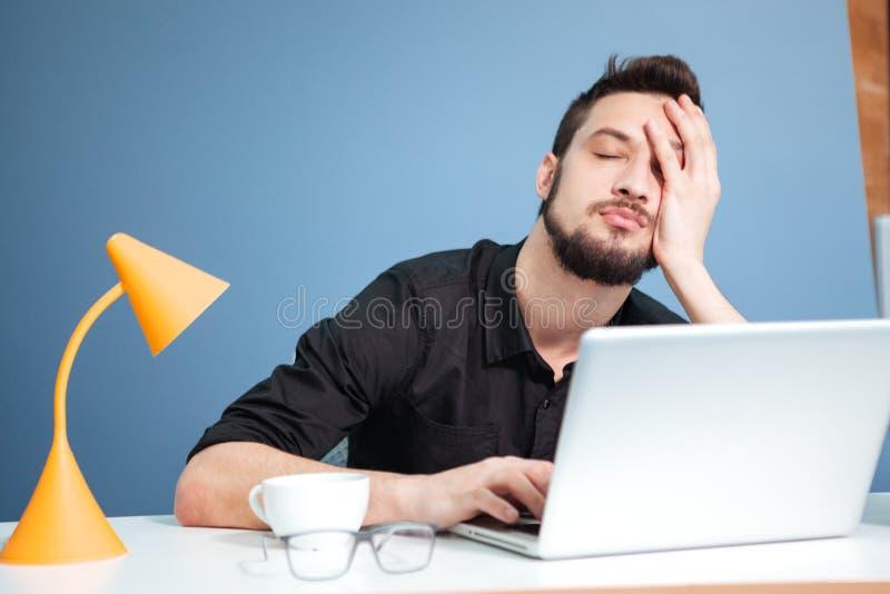 Trött affärsman som sover på tabellen arkivfoton