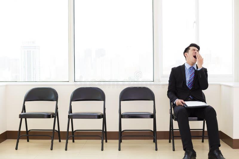 Trött affärsman som väntar på stolen royaltyfri foto