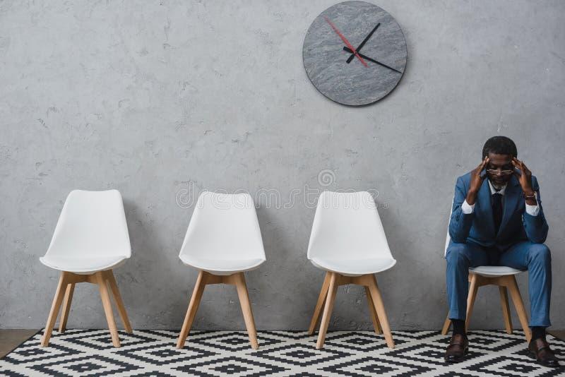 Trött affärsmansammanträde i ett väntande rum och rörande huvud med händer och att ha royaltyfria foton