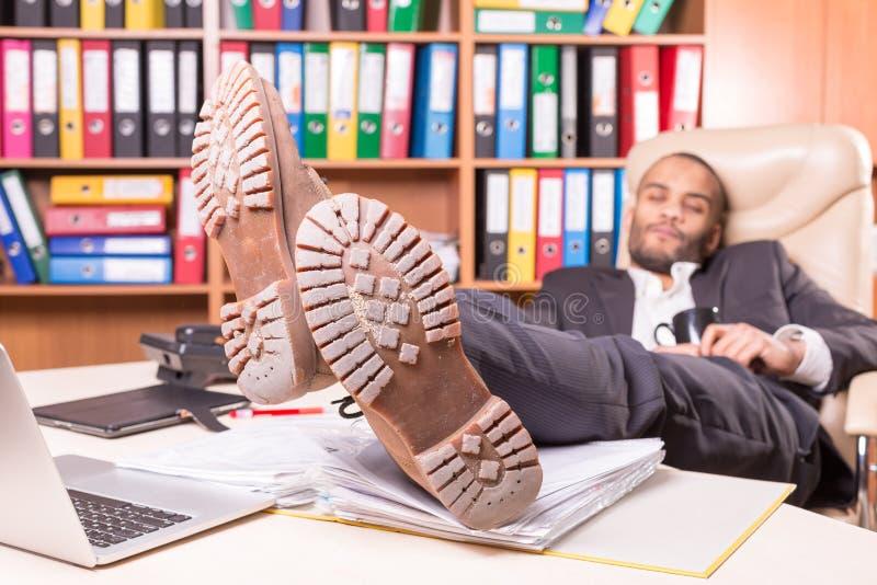 Trött afrikansk man som sover i kontoret royaltyfria bilder