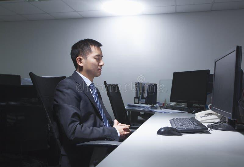 Trött arbetare för vit krage som i regeringsställning sitter framme av datoren fotografering för bildbyråer