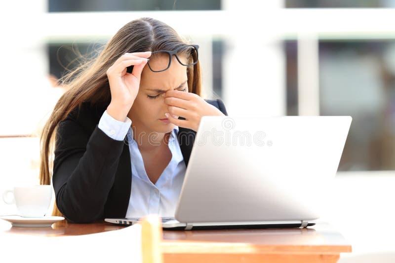 Trött arbetarlidandeeyestrain i en coffee shop arkivfoton