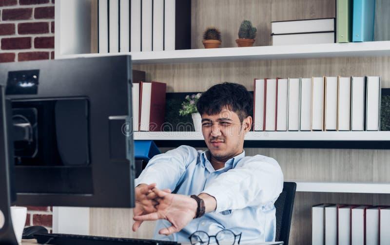 Trött asiatisk affärsman som framme sträcker av den skrivbords- datoren i modernt kontor, når att ha arbetat hela dagen arbeta so arkivbild