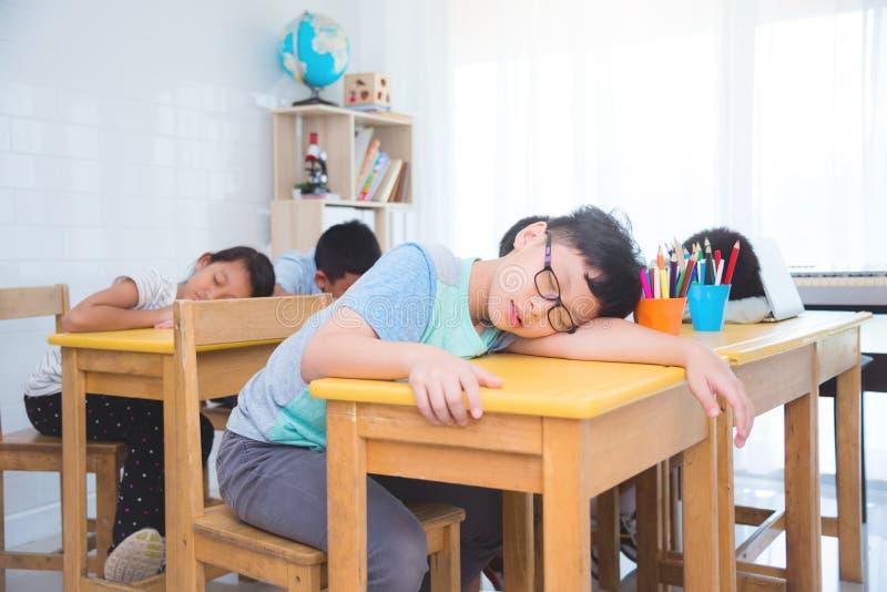 Trött asiatisk grundskolastudent som sovande faller stundstudie royaltyfri fotografi