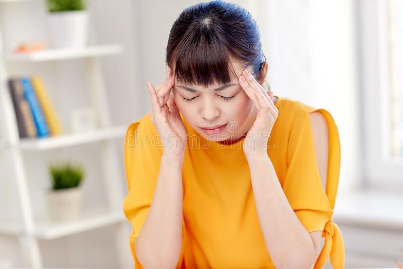 Trött asiatiskt kvinnalidande från huvudvärk hemma arkivfoto