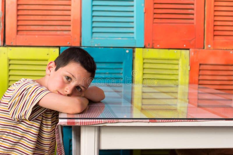 Trött barn som vilar på tabellen royaltyfri fotografi
