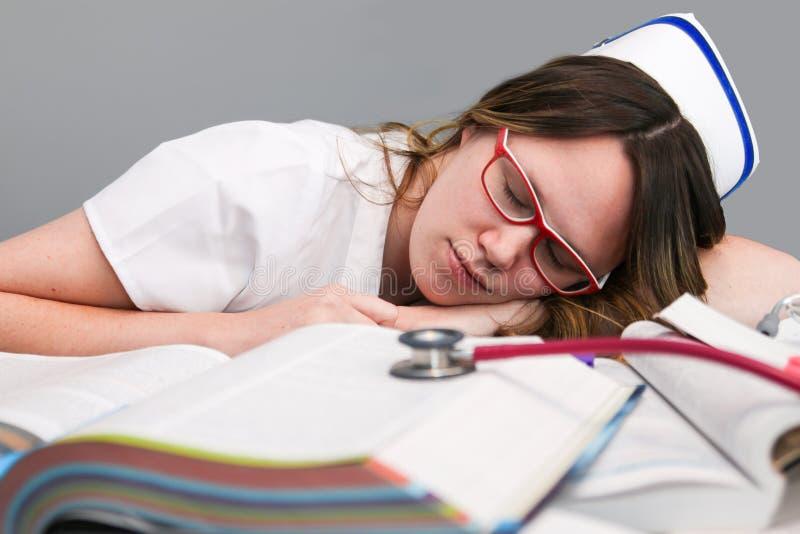 Trött barnsjuksköterska med locket som sover royaltyfri foto