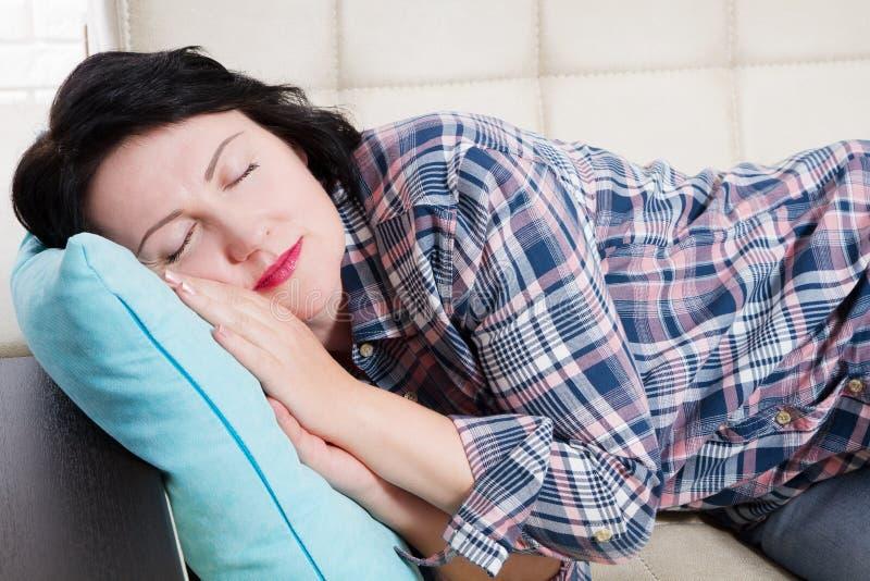 Trött brunett för stående som sover att ligga på en soffa i vardagsrummet hemma efter arbete, mellersta åldrig kvinna arkivfoto