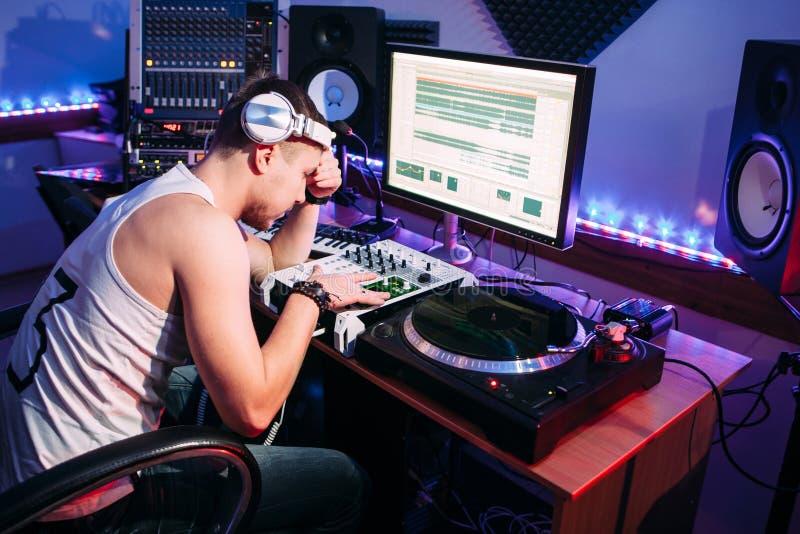 Trött discjockey efter övertid i studio royaltyfria bilder