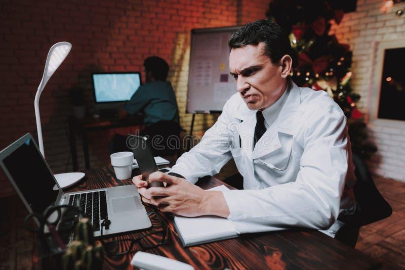 Trött doktor med minnestavlan i regeringsställning på helgdagsafton för nytt år royaltyfri bild