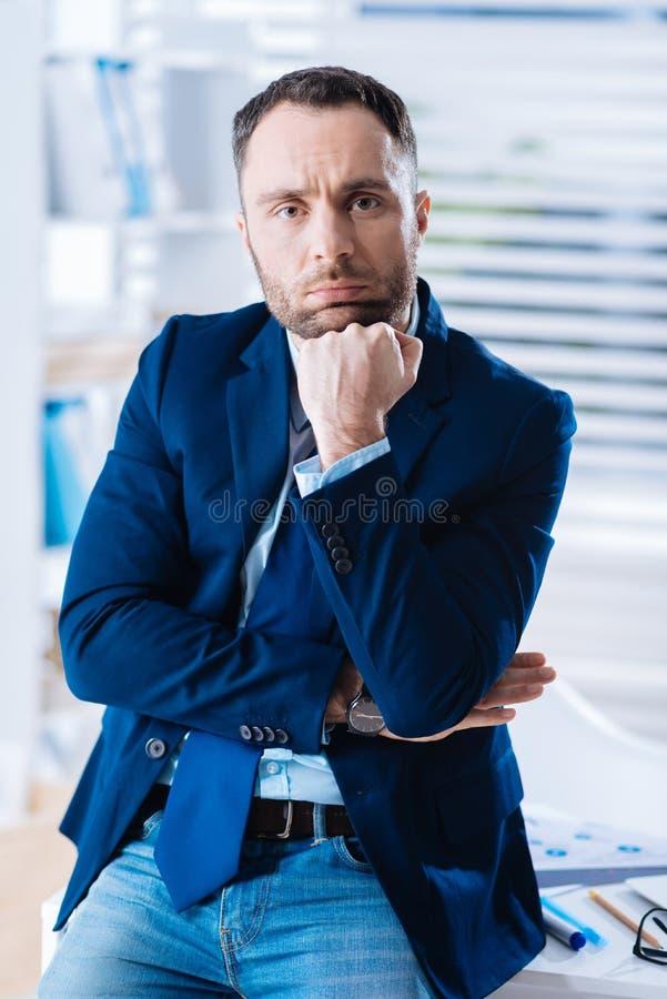 Trött dyster affärsman som ser uppriven, medan sitta bara i hans kontor arkivbild