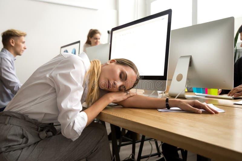 Trött eller uttråkad kvinnlig anställd som sovande ligger på kontorsarbetsplatsen royaltyfri fotografi