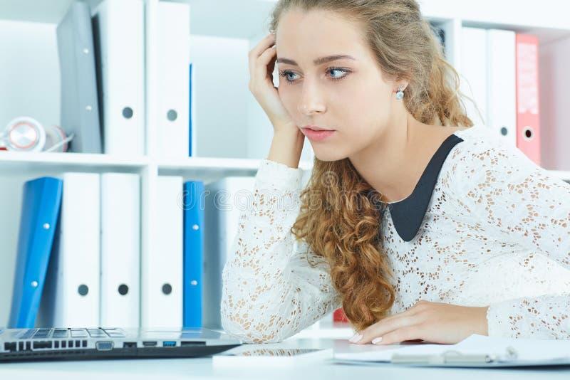 Trött eller uttråkat ungt Caucasian kvinnasammanträde på kontorsskrivbordet framme av bärbar datordatoren royaltyfri foto